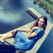 Portrait image of romantic young brunette pretty lady having fun relaxing sitting in casual blue dress on river or lake pier dreaming on summer sunny day outdoors copy space background — Stock Photo #53107401