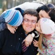 Happy family of 4 celebrating closeup portrait: Parents with two children having fun hugging & kissing father who is happy smile & looking at camera on spring or autumn day outdoors background — Stock Photo #53109913