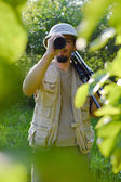 Journey on safari tour: portrait of tourist or exploring scientist male in pith helmet having fun observing looking through scope  on summer sunny day green woods copy space background — Photo