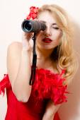 Beautiful glamor young blond lady sexy attractive pin up girl having fun looking peering in spyglass telescope at copy space with red flower in her hair on white background closeup portrait image — Stock Photo
