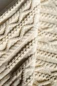 Closeup detail of woven handicraft knit woolen design texture and knitting needle. Fabric white copy space background — Stock Photo