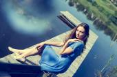 Portrait image of romantic young brunette pretty lady having fun relaxing sitting in casual blue dress on river or lake pier dreaming on summer sunny day outdoors copy space background — Stock Photo