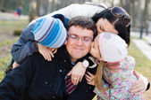 Happy family of 4 celebrating closeup portrait: Parents with two children having fun hugging & kissing father who is happy smile & looking at camera on spring or autumn day outdoors background — Stock Photo