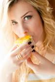 Closeup picture of eating alone large fruit creamy cake beautiful blond young lady sexy green eyes girl having fun happy smiling & looking at camera on bedroom background portrait — Stock Photo