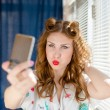 Close up on taking funny selfie or selfy photo with smart phone beautiful young pinup lady having fun by window with white blinds over sun light rays copy space background portrait picture — Stock Photo #53640683