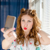 Close up on taking funny selfie or selfy photo with smart phone beautiful young pinup lady having fun by window with white blinds over sun light rays copy space background portrait picture — Stock Photo