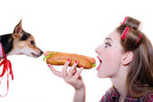 Girl eating a hot dog and cute dog looking hungry — Stock Photo