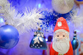 Glass toys on faux pine tree and Santa Claus — Stock Photo