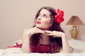 Girl with red lipstick relaxing in bed looking up — Stock Photo