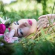 Woman lying gracefully on green grass — Stock Photo #53742407
