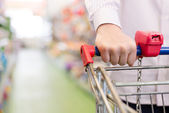 Man or woman in shop with shopping trolley or cart, closeup on hand on the supermarket shelf background — Foto Stock