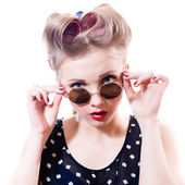 Pinup girl looking at camera over sunglasses — Stock Photo