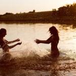Teenage girls splashing water in river — Stock Photo #54072935
