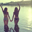 Two girls in bikini holding hands up to sky — Stock Photo #54099547