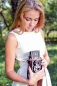 Girl holding and looking at retro camera — Stock Photo