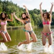 Three young women jumping high in the water — Stock Photo #54168135