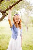 Blond young woman standing under blooming tree — Stock Photo