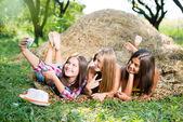 Girls lying on hay and making selfish — Stock Photo