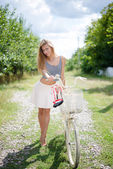 Girl standing with a bicycle on country road — Stockfoto