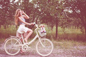 Young woman cycling on country road — Stockfoto