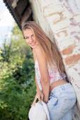 Blonde lady posing on countryside barn wall — Stock Photo