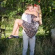 Man carrying woman on arms and hugging outdoors — Stock Photo #55309349