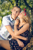 Portrait of happy young couple in bohemian style kissing in autumn orchard on green trees outdoors background — Stock Photo