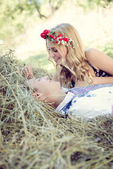 Young couple hugging on haystack on green outdoors — Fotografia Stock