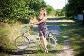 Woman cycling on country road near apple garden — Stock Photo