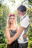Young couple hugging in autumn orchard — Stock Photo