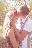 Happy couple kissing in autumn orchard — Stock Photo