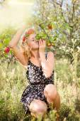 Blond girl smiling among red apples outdoors — Stockfoto