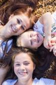 Three happy sisters of 3, 13 and 20 years old lying on blanket looking up at camera and smiling joyfully — Stock Photo