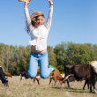 Joyful cowgirl: active beautiful young woman in jeans and white shirt having fun jumping high with hat in hand among cows looking to camera on blue sky copy space background — Stock Photo #56050571