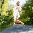 Sexy pretty girl in mini dress jumping high and happy smiling on blue sky outdoors copy space background portrait — Stock Photo #56051203