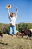 Joyful cowgirl: active beautiful young woman in jeans and white shirt having fun jumping high with hat in hand among cows looking to camera on blue sky copy space background — Stockfoto