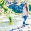 Young woman standing on cliff edge over fast mountain river on summer or early autumn outdoor copy space background — Stock Photo #56060275