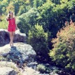 Young woman standing on cliff edge over fast mountain river on summer or early autumn outdoor copy space background — Stock Photo #56061585