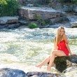 Young woman sitting on rock in fast mountain river and splashing water on summer or early autumn outdoor copy space background — Stock Photo #56067211