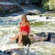 Young woman sitting on rock in fast mountain river and splashing water on summer or early autumn outdoor copy space background — Stock Photo #56067535