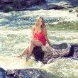 Young woman sitting on rock in fast mountain river and splashing water on summer or early autumn outdoor copy space background — Stock Photo #56067807