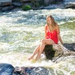 Young woman sitting on rock in fast mountain river and splashing water on summer or early autumn outdoor copy space background — Stock Photo #56068129