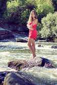 Young woman standing on rock in fast mountain river on summer or early autumn outdoor copy space background — Stok fotoğraf