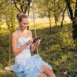 Beautiful young woman in prom dress sitting on swings and typing on tablet pc on green summer or autumn outdoors copyspace background — Stock Photo #58505587