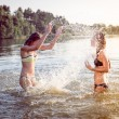 Summer fun: filtered image of 2 beautiful young woman or teenage girls best friends having fun and splashing water in river or lake at sunset on sunny outdoors copy space background — Stock Photo #58505615