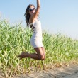 Sexy pretty girl in white mini dress jumping high and happy smiling on blue sky outdoors copy space background portrait — Stock Photo #58505627