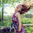 Portrait of beautiful blond young woman having fun playing with long hair & looking at camera on green summer copy space outdoors background — Stock Photo #58507321