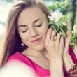 Close up portrait of beautiful blond young woman pretty girl with blue eyes standing under blooming tree & looking at camera on picture — Stock Photo #58507325
