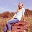 Girl sitting on suitcases — Stock Photo #58536139