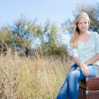 Girl sitting on retro suitcases — Stock Photo #58536149